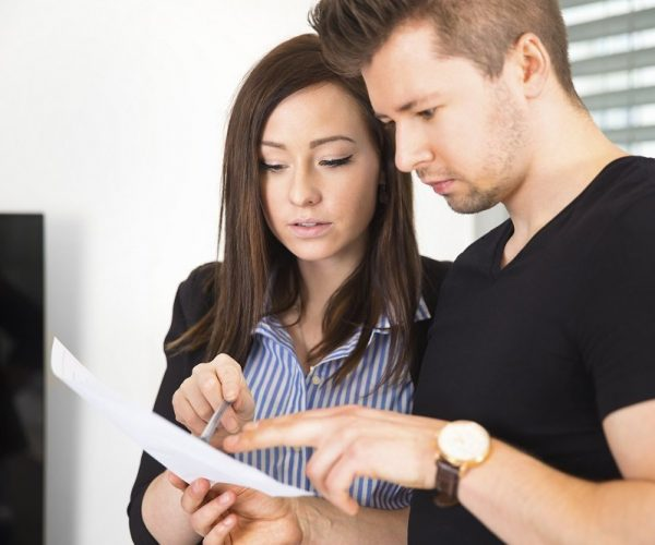 Confident male and female business people reading document in office