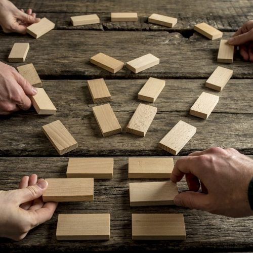Business teamwork and bright ideas concept with a group of business people arranging wooden blocks into the shape of a light bulb on an old rustic table, close up view of their hands.