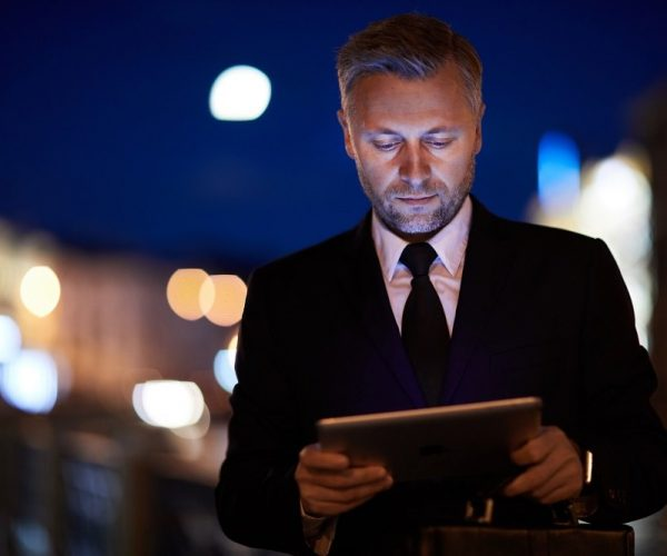 Contemporary mobile businessman with touchpad watching through websites in the evening in urban environment
