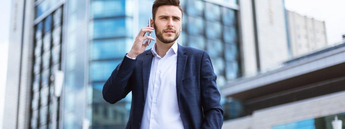Serious millennial businessman talking on smartphone near skyscraper at street