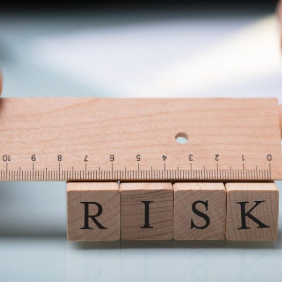 Close-up Of A Businessperson's Hand Measuring Risk Blocks With Wooden Ruler