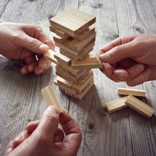 Planning, risk and team strategy in business, businessman gambling placing wooden block on a tower