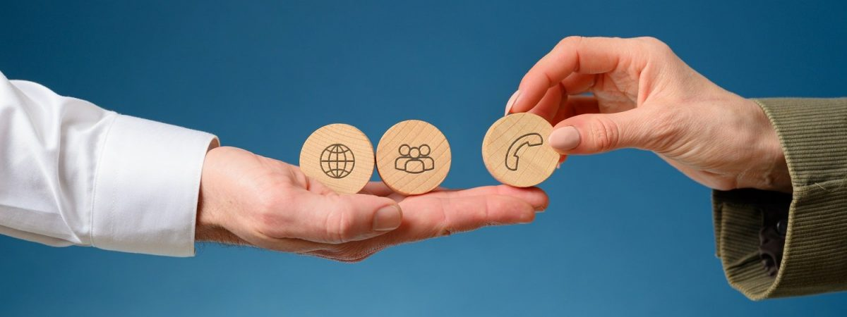 Female hand placing three wooden cut circles with contact and communication icons on them on a businessmans hand.